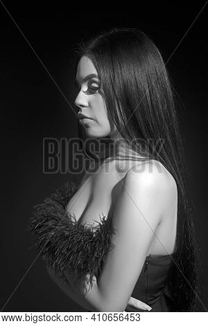 Attractive And Sexy Portrait Of A Long Hair Young Woman In Black Dress In Studio. Naked Back. Fashio