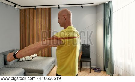 Athletic 46 Year Old Man Working Out At Home With Rubber Band. Man Conducting A Training Session On