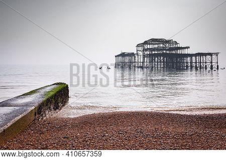 Brighton Beach And The Remains Of The Old West Pier On A Foggy Day In Flat Light, Sussex, England, U