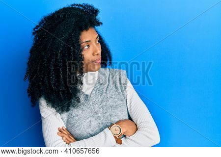 African american woman with afro hair wearing casual winter sweater looking to the side with arms crossed convinced and confident
