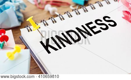 Kindness - Text On A Notepad With Wrinkled Paper And Paper Needles On Wooden Background.