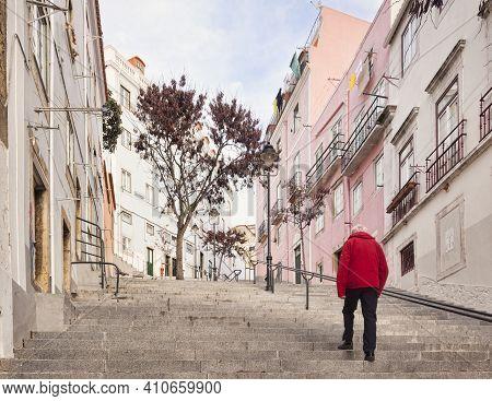 27 February 2018: Lisbon, Portugal - Man In Red Jacket Walking Up Steep Steps Typical Of Lisbon, Por