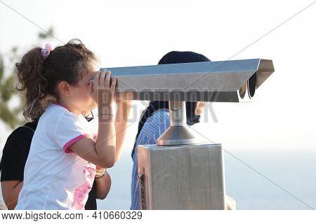 Child Girl Wathching Through Telescope Outdoors. Kid Enjoying Sea View Using Panoramic Telescope. Tr