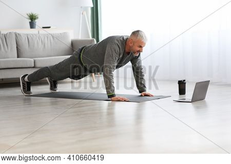 Sporty Bearded Middle-aged Man Doing Exercises At Home, Using Laptop, Watching Sport Videos Online A