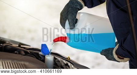 Man With Gloves Pouring Antifreeze Coolant Into Car Reservoir In Winter Season.