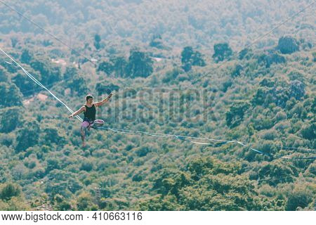 A Woman Is Walking Along A Stretched Sling. Highline In The Mountains. Woman Catches Balance. Perfor