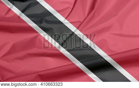 Fabric Flag Of Trinidad And Tobago. Crease Of Trinidadian Flag Background, A Red Field With A White-