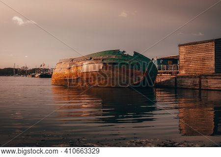 Old Derelict Boat Sinking Alongside Jetty. Sinking Boat During A Sunset In Winter.
