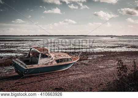 Old Boat On The Beach. Isolated Boat On A Shingle Beach During Mid Day Winter Sun While Tide Was Out