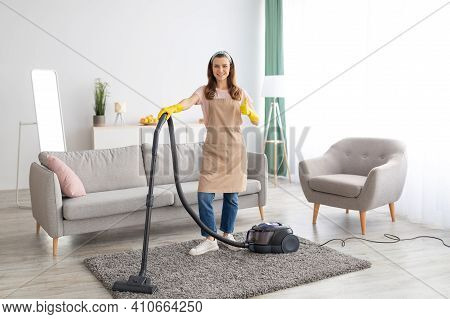 Full Length Portrait Of Female Cleaning Service Specialist Showing Thumb Up Gesture, Standing With V