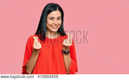 Beautiful young woman wearing casual clothes doing money gesture with hands, asking for salary payment, millionaire business