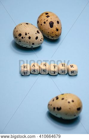 Quail Eggs Next To Inscription Easter Made From Wooden Cubes. Small Quail Eggs On Blue Background. B