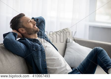 Closeup Of Carefree Bearded Man In Casual Clothes Relaxing On Couch At Home, Looking At Copy Space,