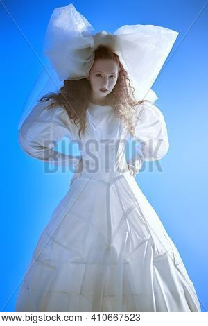 Fashion art portrait of a girl looking like a doll with lush red curly hair posing in a white haute couture dress and a huge bow. Studio portrait on blue background.