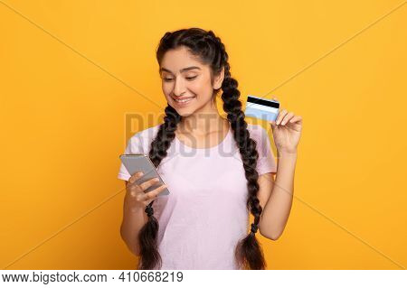 Online Payment. Frontal Portrait Of Smiling Indian Woman Holding And Showing Debit Credit Card, Usin