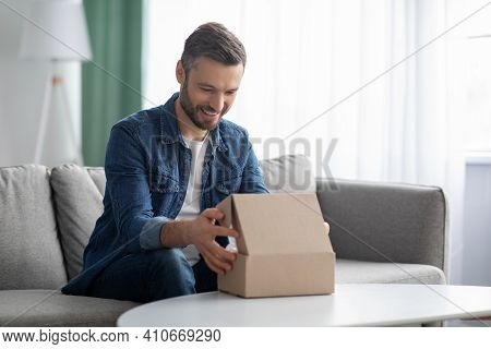 Happy Middle-aged Man Unpacking Delivery Box, Sitting On Couch By Tea Table, Home Interior. Satisfie