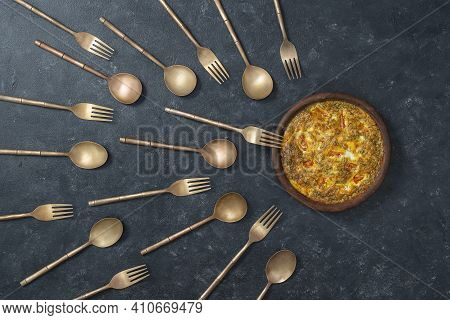 Ceramic Bowl With Vegetable Frittata And Brass Forks And Spoons Look Like Sperm Competition. Spermat