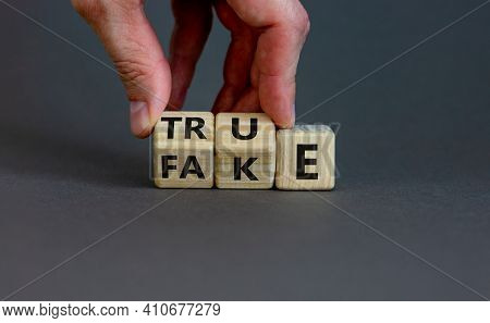 Fake Or True Symbol. Businessman Flips Wooden Cubes And Changes The Word 'fake' To 'true' Or Vice Ve