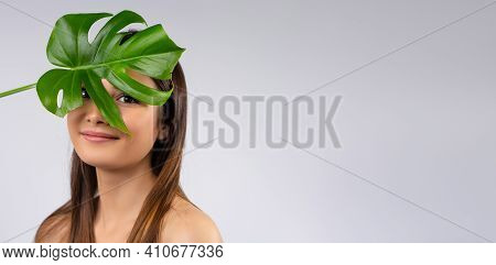 Beautiful Girl With Brown Eyes, With Natural Makeup, Has Exotic Leaves Next To Her Face. Beauty, Fas
