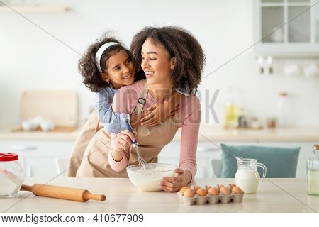 Baking With Mother Is Fun. Happy African American Woman And Her Little Daughter Mixing Flour And Dou