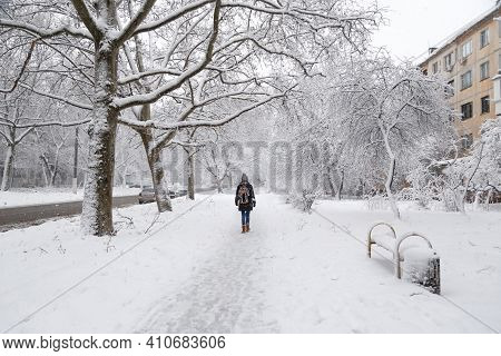 Young Woman With Backpack Walking At Snow-covered Winter Street, Back View. Snowy Winter
