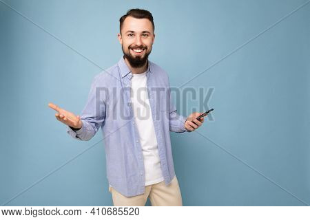 Happy Smiling Handsome Young Brunette Unshaven Man With Beard Wearing Stylish White T-shirt And Blue