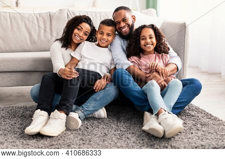Happy Loving Family. Portrait Of Cheerful African American Man And Woman Sitting On The Floor Carpet