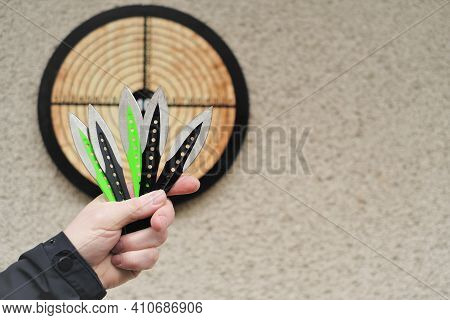 Throwing Knives. Sport And Hobby . Throwing Knives In A Mans Hand Close-up And A Target On The Wall.