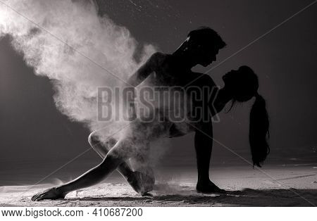 Two Ballet Dancers Perform Dance On The Floor Covered Flour Against Background Of White Flour Cloud