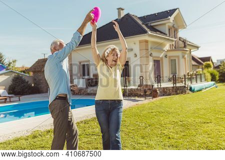 Active Senior Couple Having Fun Spending Sunny Summer Day Outdoors, Playing Catch And Toss On The Ba