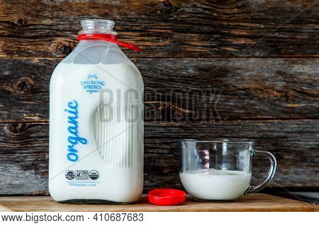 NORWALK, CT, USA-MARCH 3, 2021:   Glass bottle with organic milk from Trickling Springs organic milk in kitchen with rustic looking wooden background.