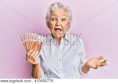 Senior grey-haired woman holding 100 norwegian krone banknotes celebrating achievement with happy smile and winner expression with raised hand