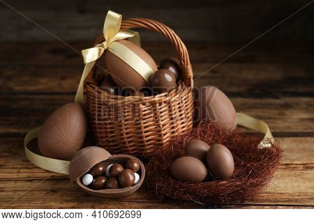 Composition With Tasty Chocolate Eggs, Wicker Basket And Decorative Nest On Wooden Table