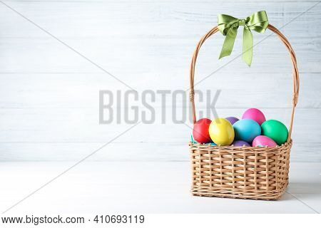 Colorful Easter Eggs In Wicker Basket On White Background. Space For Text