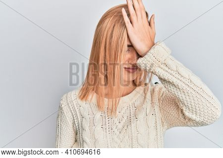 Beautiful caucasian woman wearing casual winter sweater surprised with hand on head for mistake, remember error. forgot, bad memory concept.