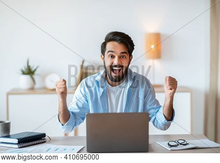 Portrait Of Overjoyed Eastern Man Celebrating Success With Laptop In Office, Excited Arab Guy Emotio