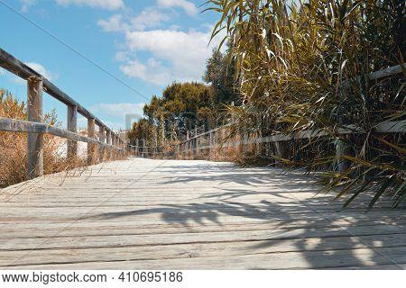 Wooden Empty Board Walk Leading Through Sand Dunes To Mediterranean Sea And Beach Of Los Arenales De