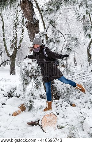 Smiling Young Woman Standing On Fallen Tree After Sleet Load And Snow In A Snow-covered Winter Park.