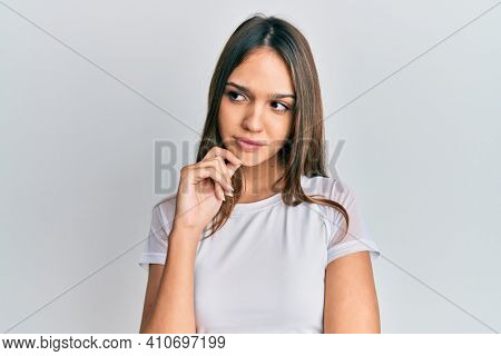 Young brunette woman wearing casual white t shirt thinking concentrated about doubt with finger on chin and looking up wondering