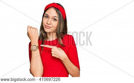 Young brunette woman wearing casual clothes in hurry pointing to watch time, impatience, looking at the camera with relaxed expression