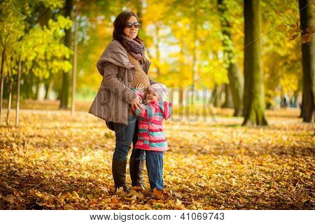 A pregnant woman and child, among the beautiful autumn.