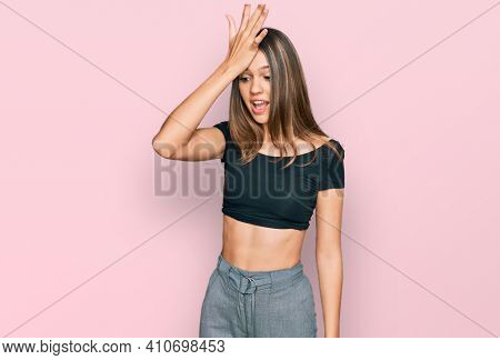 Young brunette woman wearing casual clothes surprised with hand on head for mistake, remember error. forgot, bad memory concept.