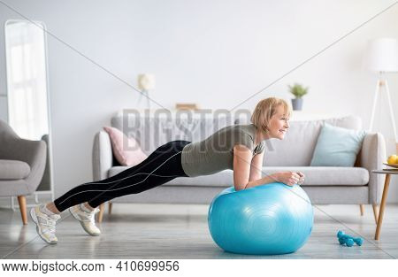 Domestic Sports During Covid-19 Concept. Athletic Mature Woman Standing In Plank On Fitness Ball, Wo