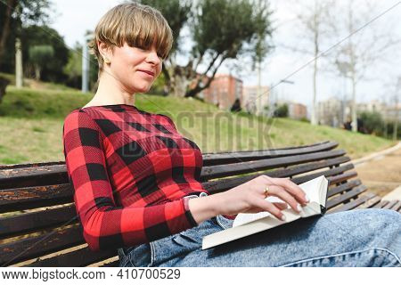 Portrait Of A Beautiful Caucasian Woman Reading A Novel Sitting On A Wooden Bench At An Urban Green