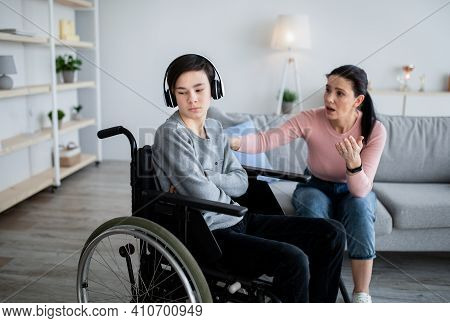 Depression In Disabled Teens. Upset Adolescent In Wheelchair Shutting Himself Off From World, His Mo