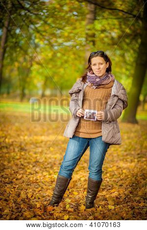 A pregnant woman, brunette, among the beautiful autumn.