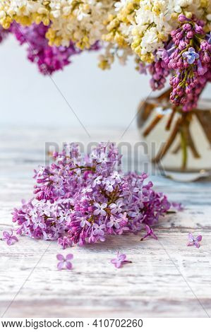 Purple Lilac In Glass Vase On White Wooden Table. Spring Branches Of Blooming Lilac Festive Bouquet