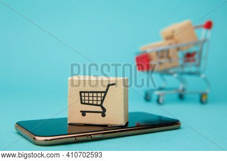 Concept Of Online Shopping. Boxes And Shopping Bag Above Smartphone Isolated On Blue Background