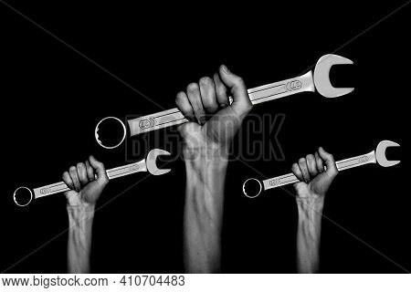 Black And White Photo. Three Spanners In The Women's Hands. Hands Holds A Wrenches On A Gray Backgro
