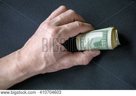 Bundle Of Rolled Up Dollar Bills Clutched In Caucasian Man's Hand. Male Holding Cash Money Currency